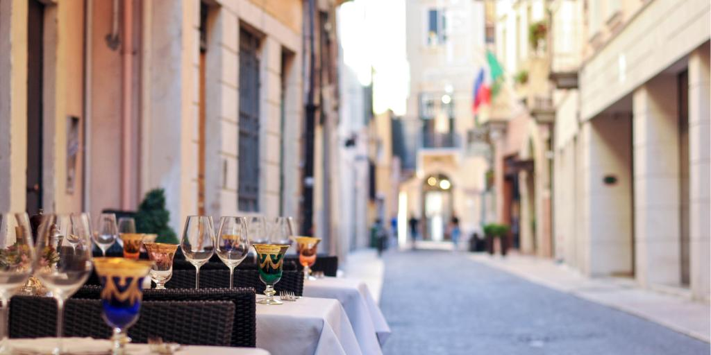 Wine glasses sitting on tables outside a restaurant on a cobbled street in Bologna, Italy