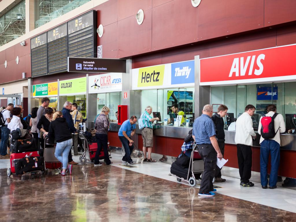 Stands of major car rental companies are at airport with customers in a queue