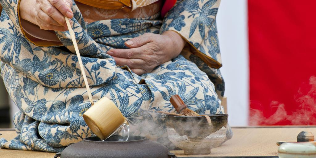 A person in a kimono performing a Japanese tea ceremony