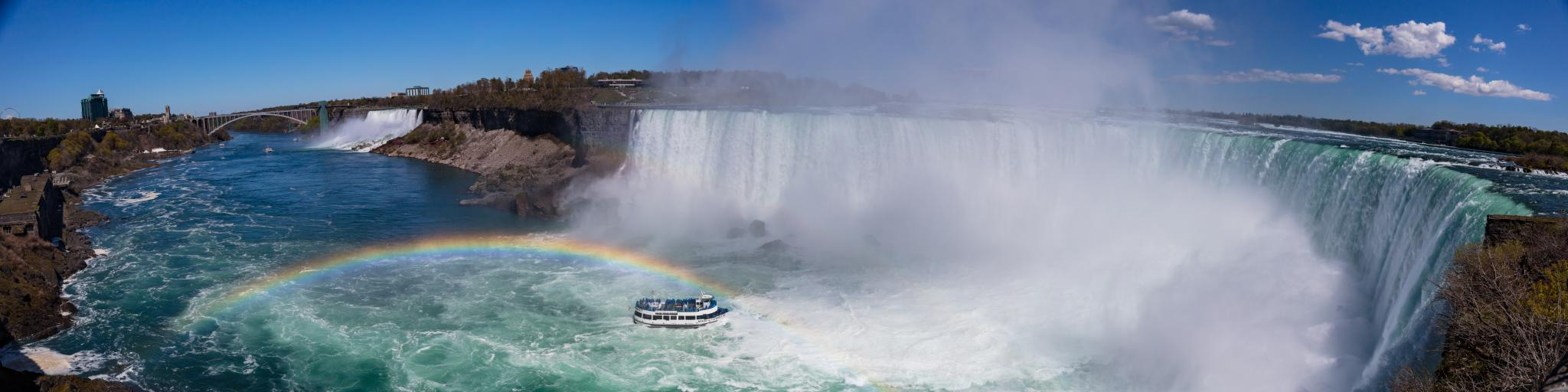 A panoramic view of Niagara Falls with a boat near the mist from the water that creates a rainbow.