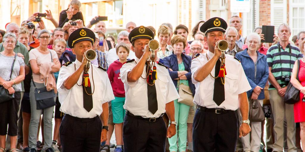 Buglers from Ypres volunteer Fire Brigade sound The Last Post with a crowd behind them