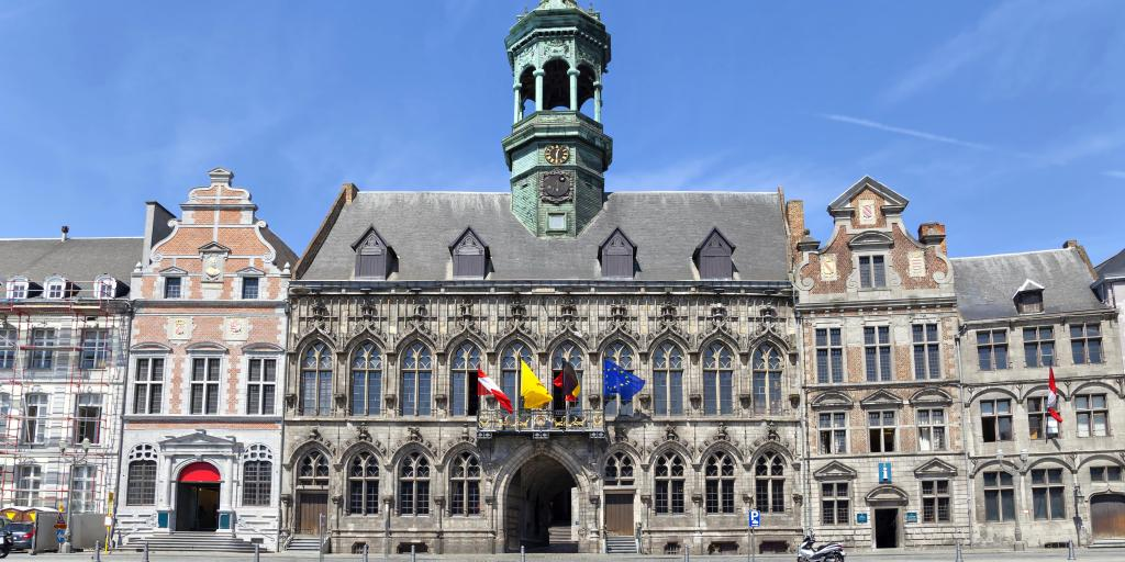 The Gothic exterior of the City Hall, Mons, Belgium, with Belgian and European flags, and a scooter parked in front