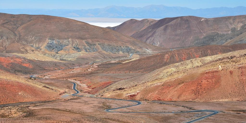 A view of the Route 52 road, Argentina, weaving through rust red mountains and desert.