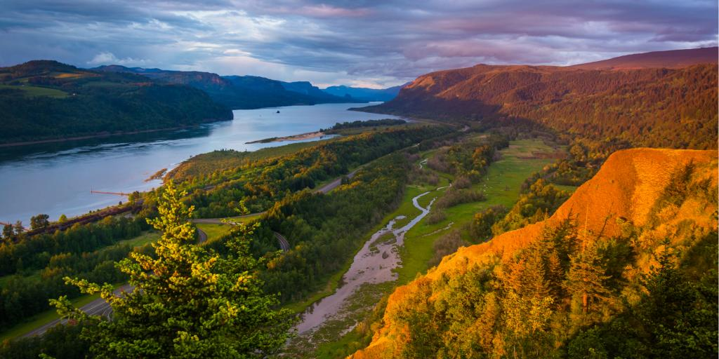 Orange light illuminates the landscape of Columbia River Gorge, Oregon, at sunset