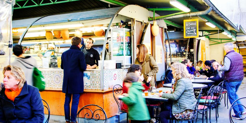 People visit the food stalls and sit at tables at Marche des Enfants Rouges, a covered market in Paris