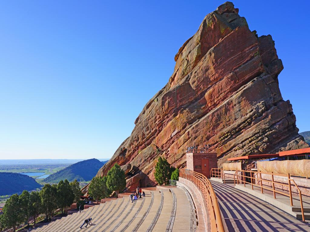 A picturesque view of the Historic open-air Red Rocks Amphitheatre with a couple of people sitting in the benches enjoying the view of the mountains from afar early in the morning in Denver