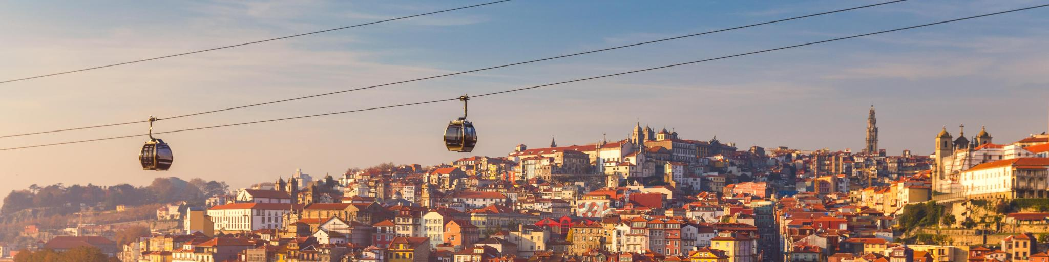 Colourful houses with red roof tiles in Porto, Portugal, with a cable car going overhead