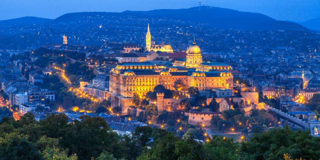 A view of Buda Castle all lit up at dusk in Budapest, with city lights in the background
