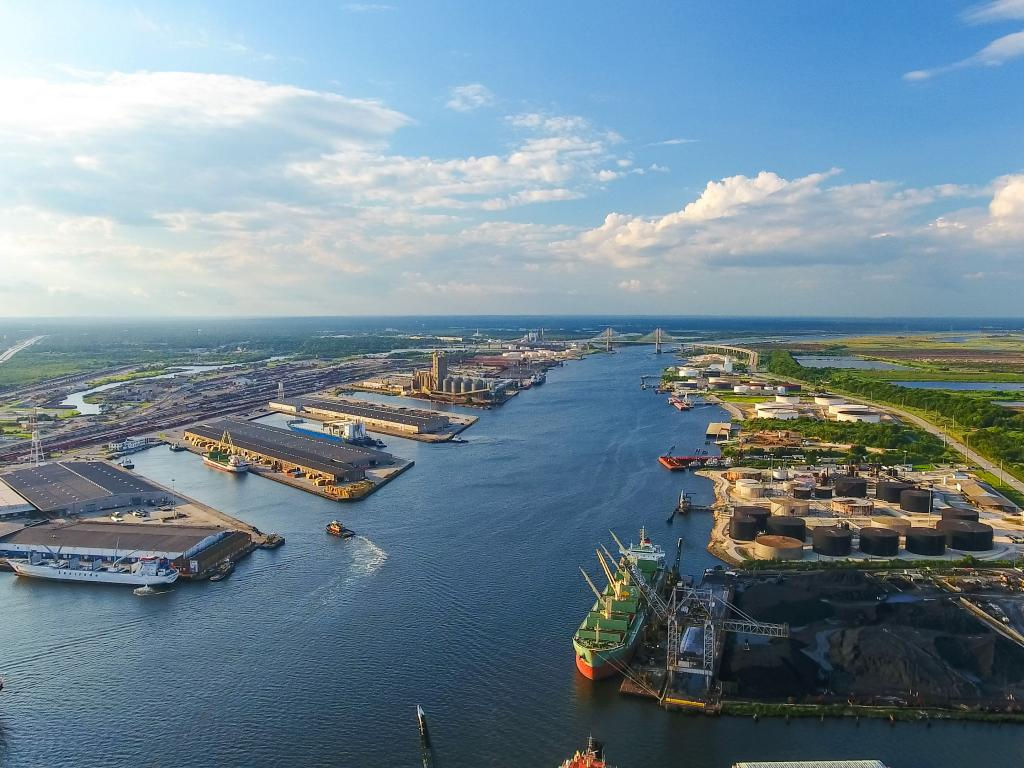 An aerial view of Mobile river and the port of Mobile, Alabama with ships dock in the harbor, green trees, and sunny weather with a sheet of white and gray clouds spread in the blue sky