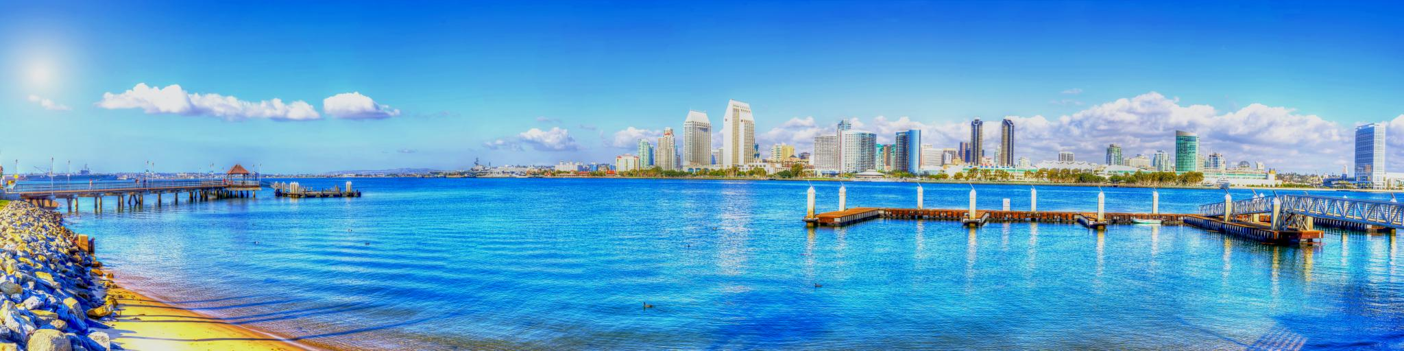 A panoramic view of the skyline of San Diego   with a thick white sheet of stretched out cotton-like clouds in a blue sky reflecting the sea in a sunny morning