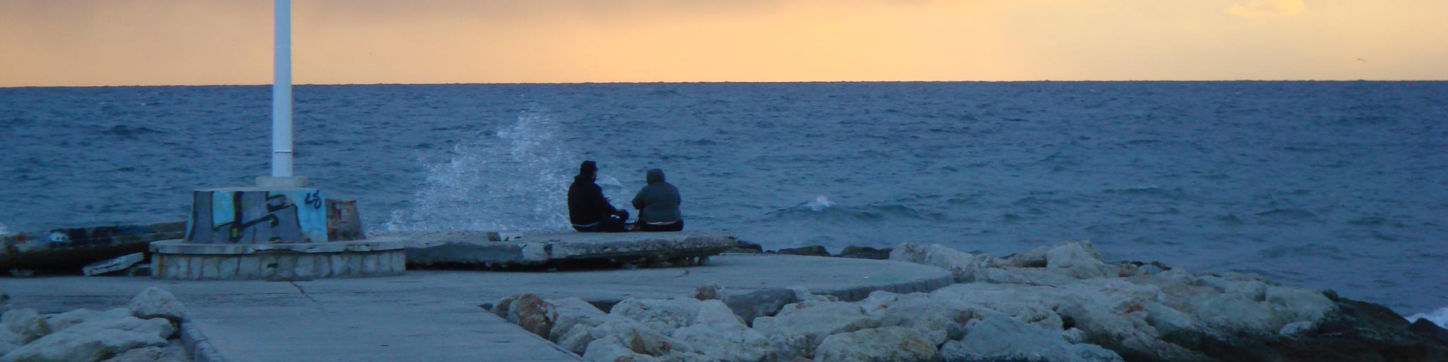 Two people watch the sun set over Pedregalejo Beach Malaga