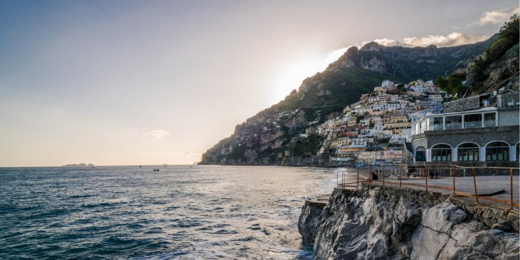 The sun sets behind a mountain at Fornillo Beach in Positano along the Amalfi Coast