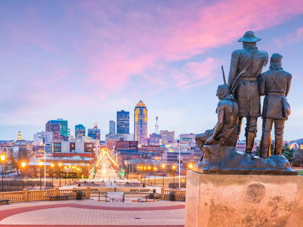 Pioneers of the Territory statue overlooking the skyline of the city of Des Moines, Iowa at sunset.