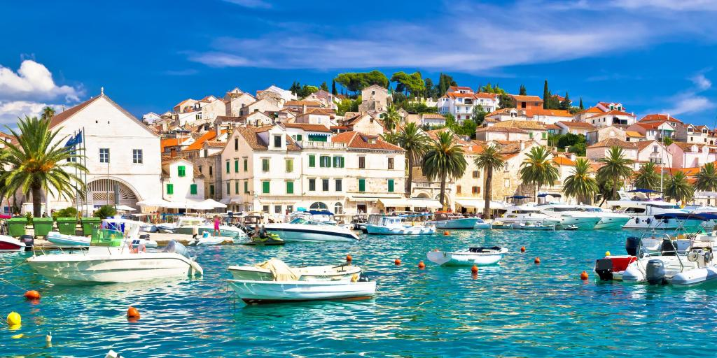 Boats in the turquoise water in the harbour of Hvar, Croatia, with white houses in the background