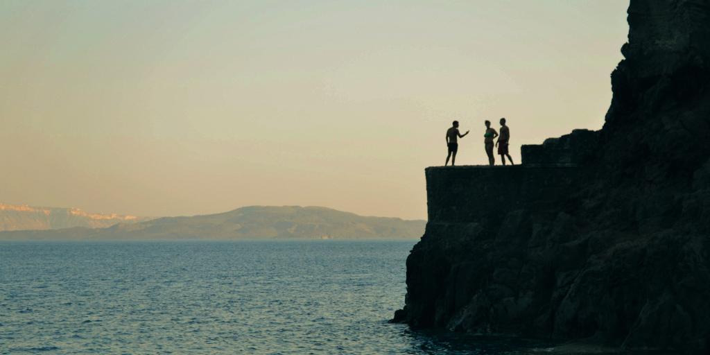 Three people stand on a cliff in Amoudi Bay, Santorini, getting ready to jump into the water