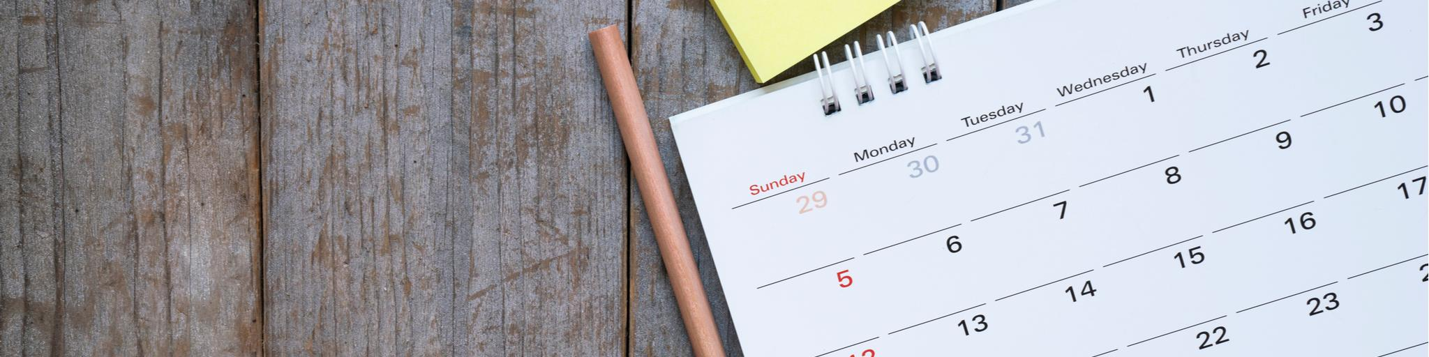 Close up of calendar on the table with pencil and sticky notes