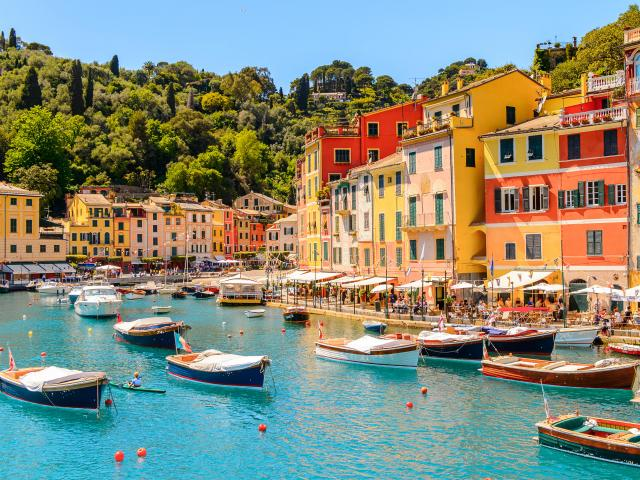 Boats in the turquoise blue water of the harbour in Portofino, Italy, with colourful townhouses in the background