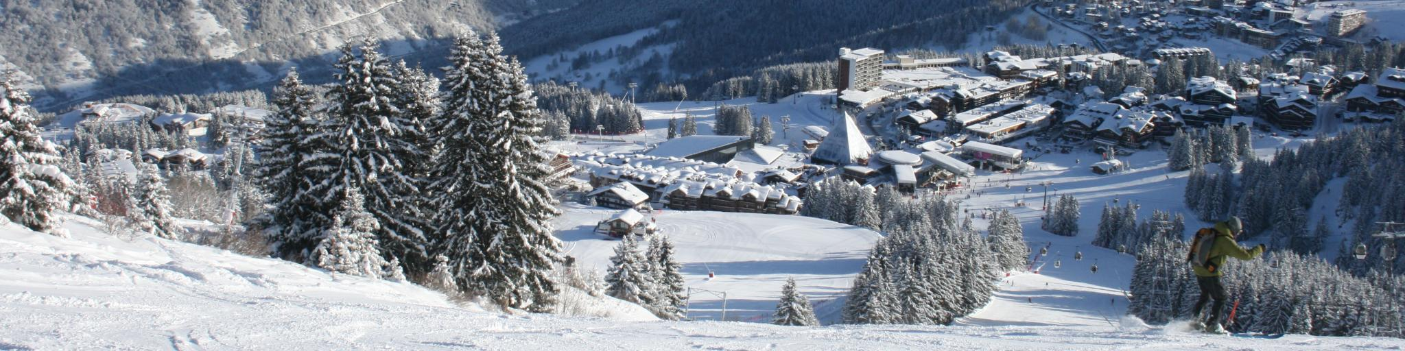 Snowy ski runs leading down to the resort town of Courchevel