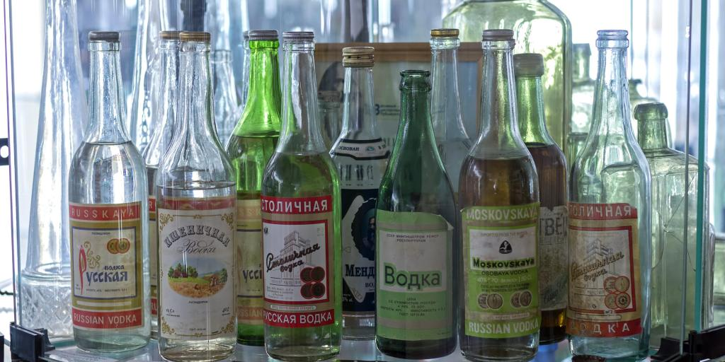 A collection of green and clear Russian vodka bottles on a shelf at the Vodka Museum, Uglich, Russia.