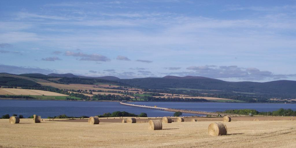 A view across hay fields and hay bails to the water in the Black Isle, Scotland.