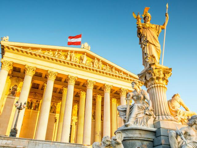 Austrian parliament building, Vienna, with Athena statue in front and an Austrian flag on top, at sunrise