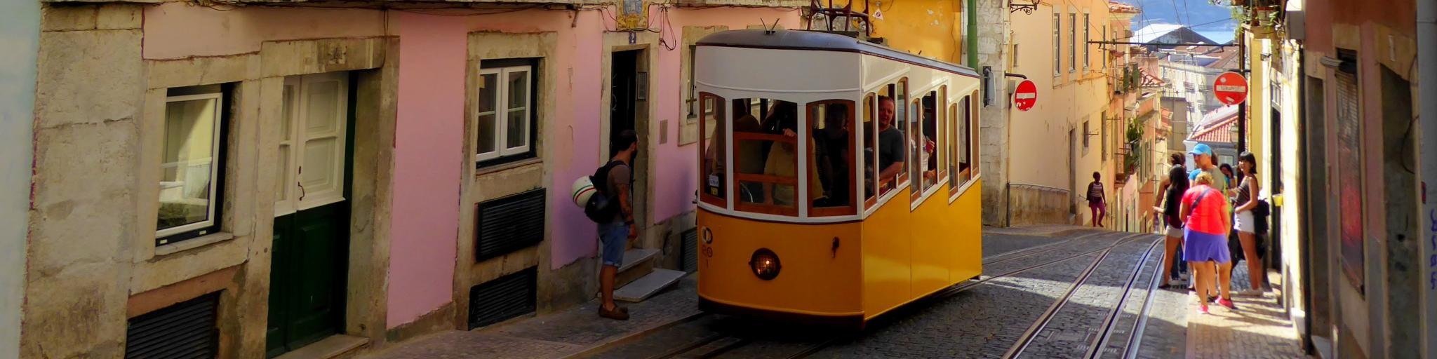 A classic yellow tram drives uphill on the streets of Lisbon, Portugal