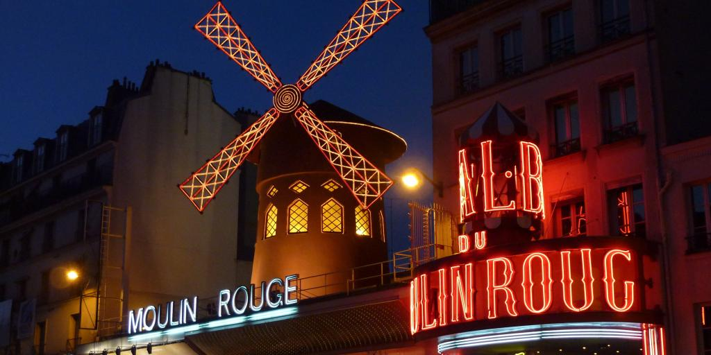 The neon lights of the Moulin Rouge lit up in the evening in Paris
