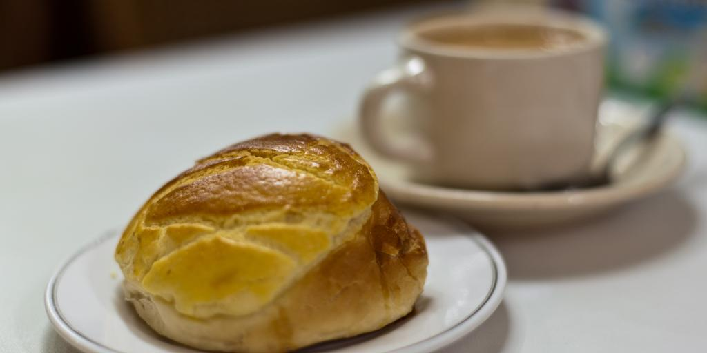 A bread roll, known as a Pineapple bun in front of a cup of tea, on a white table