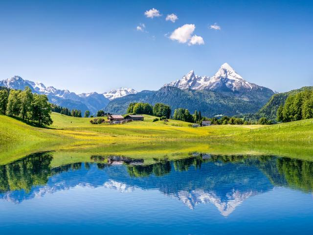 Idyllic summer landscape with the green fields and snow topped mountains reflected in a still lake