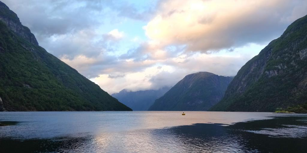 Clouds and mountains reflect in the fjord's water in Hellesylt, Norway