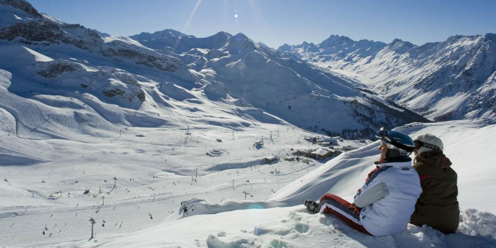 A couple sitting on a ledge looking over the ski slopes at Ischgl below