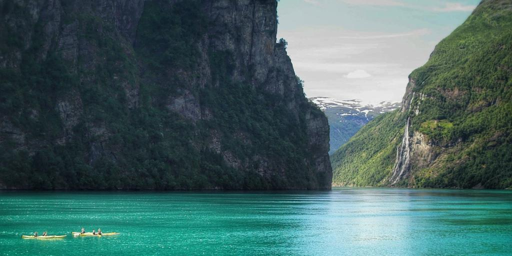 Kayakers row in the turquoise Norwegian fjord, with the Seven Sisters waterfalls in the distance