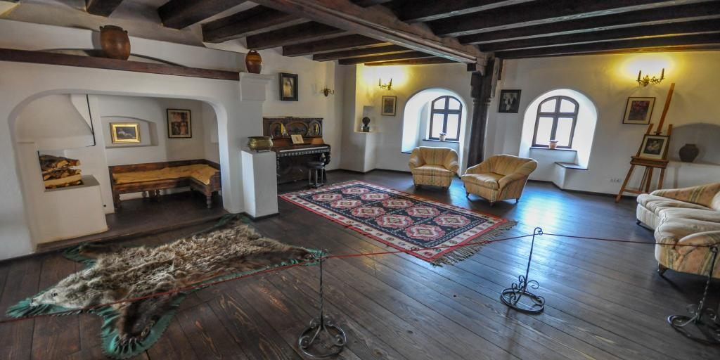 A room in Bran Castle with exposed beams, original furniture and a piano