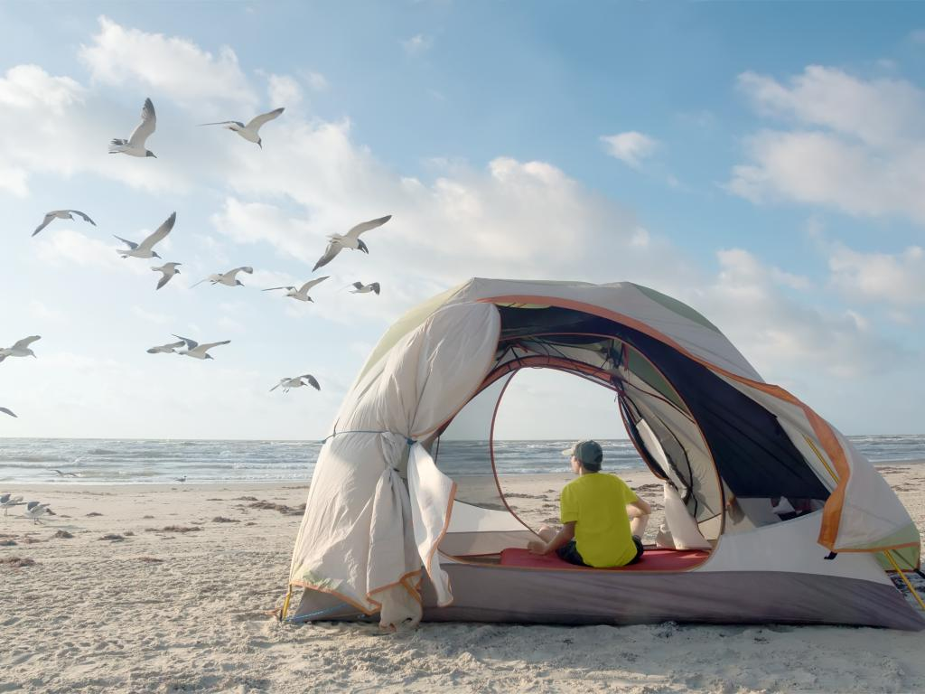 Person relaxing in a beach tent on Padre Island National Seashore with flying seagulls