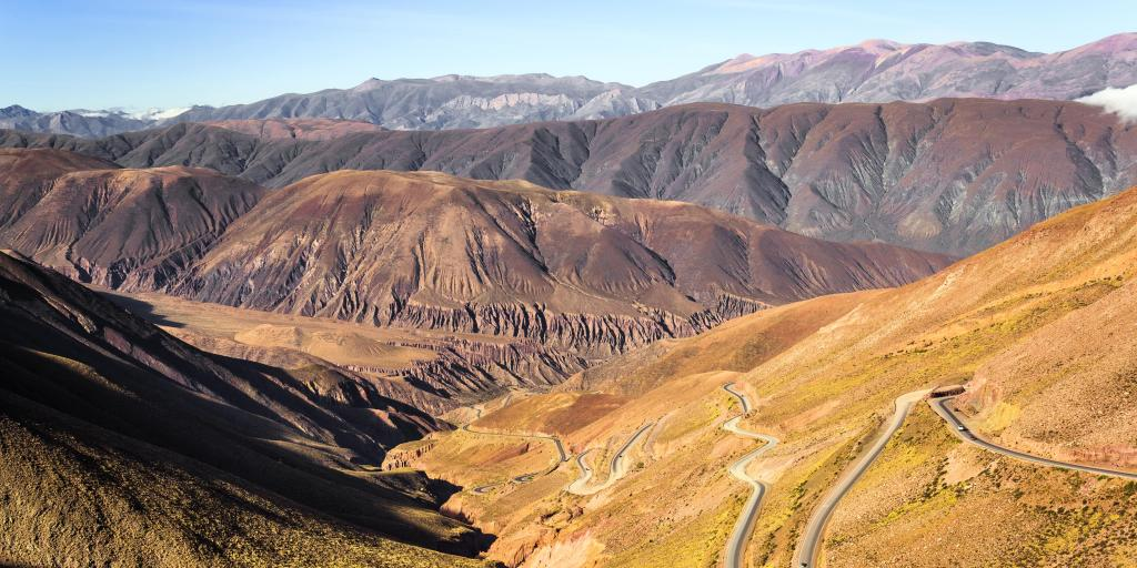 A view of the switchbacks of Cuesta de Lipan, Argentina, on a sunny day, with mountains in the background