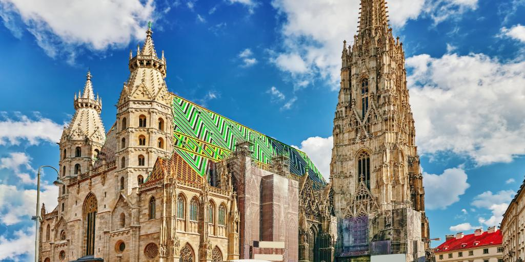 The exterior of St Stephen's Cathedral, Vienna, with a huge spire and green and blue tiled roof
