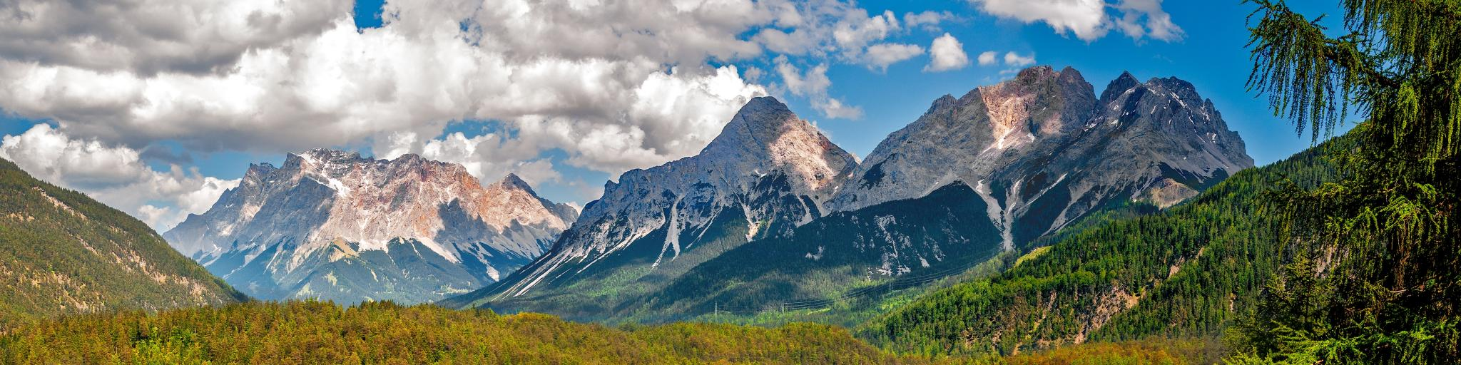 A landscape view of the mountains at Zugspitze, Austria, with forest and a lake in the foreground on a blue sky day