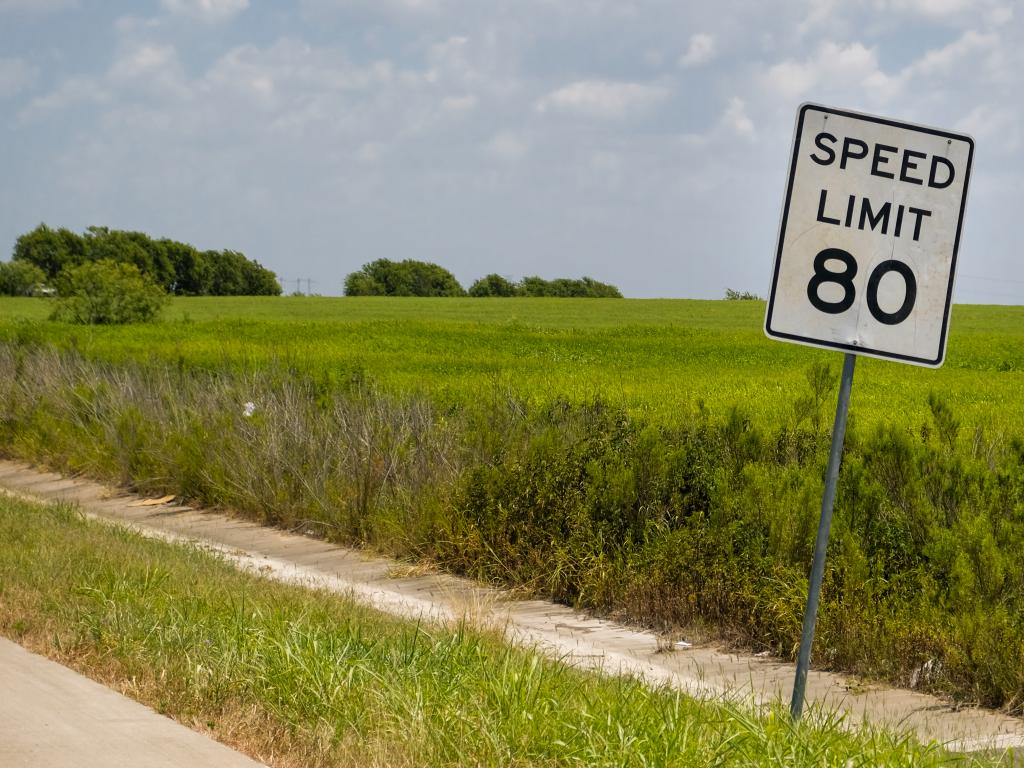 A speed limit sign by the road in Texas showing a maximum of 80 miles per hour