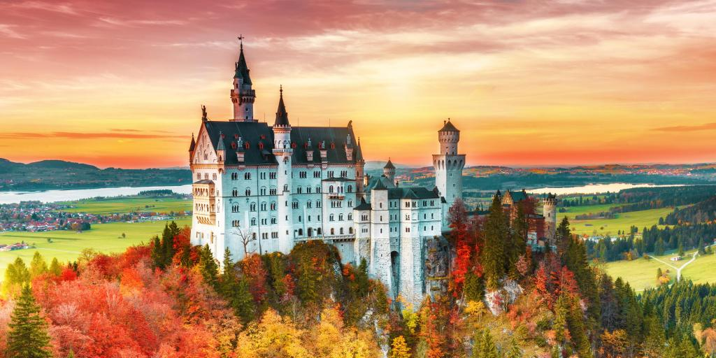 Neuschwanstein castle in Bavaria, Germany, surrounded by yellow and orange autumnal trees, at sunrise