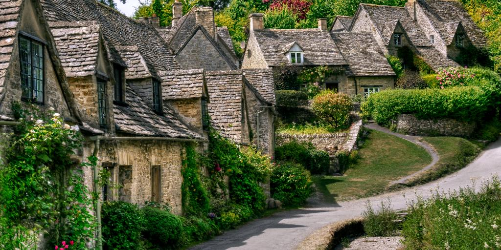 Stone cottages covered in vines line a street in the Cotswolds