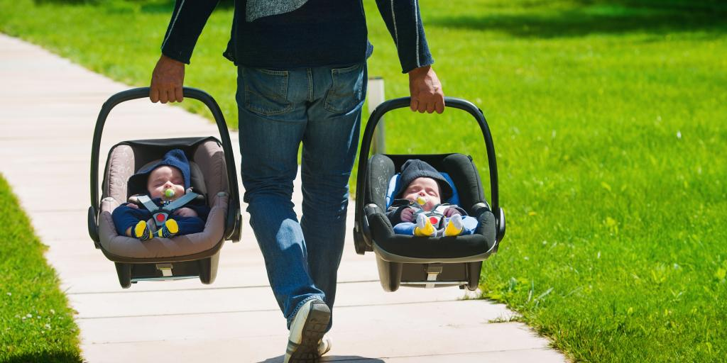 Father walking along with two babies in car seats