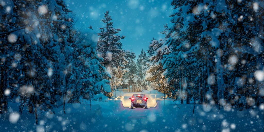 Lights of a car and winter snowy road in a dark forest at night