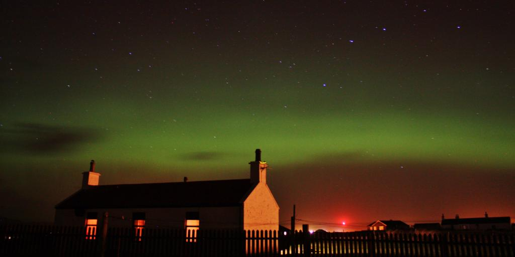 Red, green and purple Northern Lights visible in the sky above a silhouetted house in Scotland