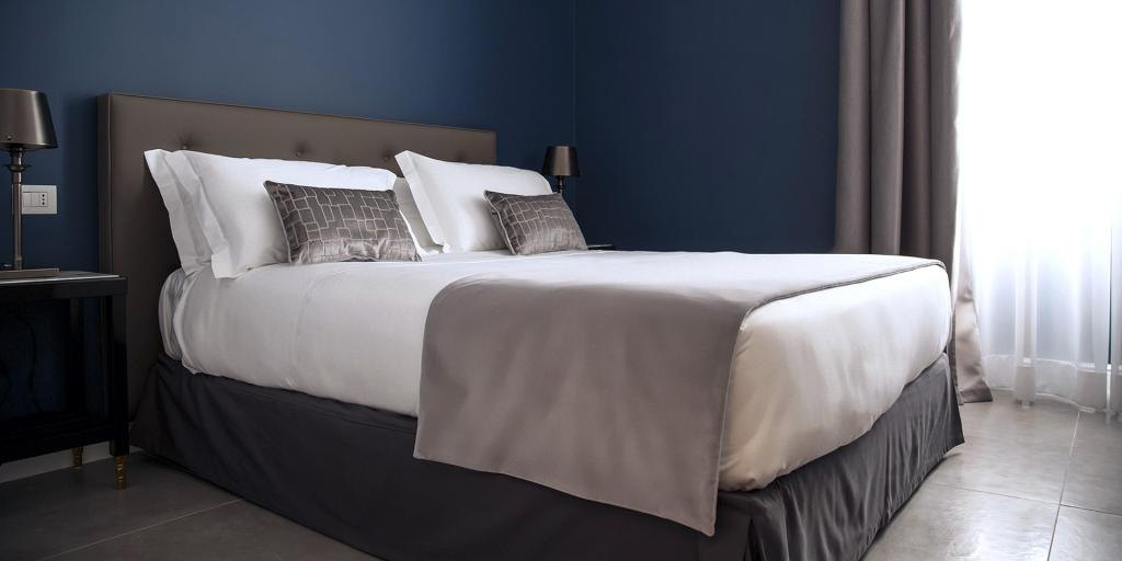 A bedroom with blue walls inside Metro 900 Hotel in Naples, Italy