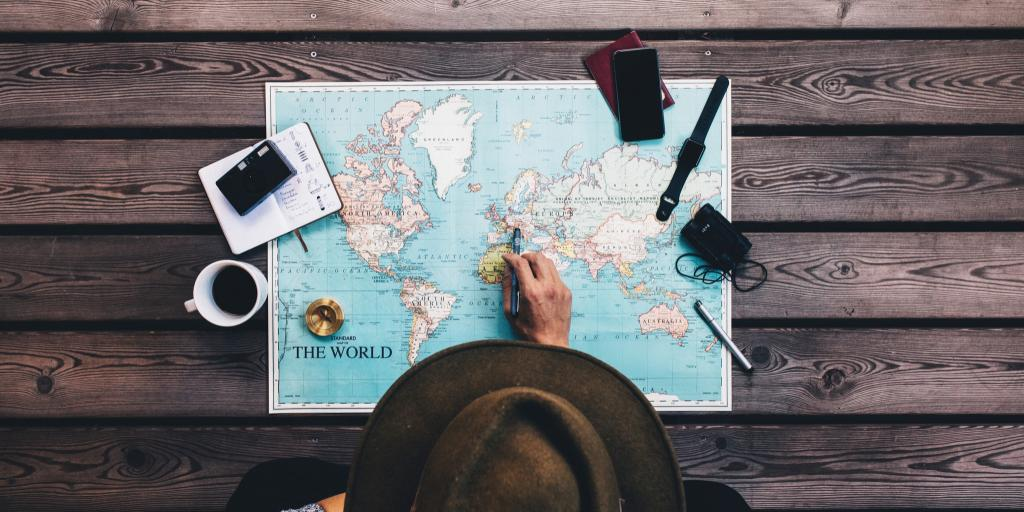 Man in a hat sits at a table looking at a map with binoculars, compass and other travel accessories