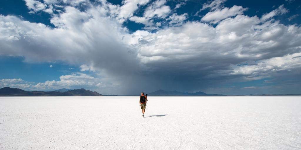 A person walks across the white expanse of the Bonneville Salt Flats in Utah, USA