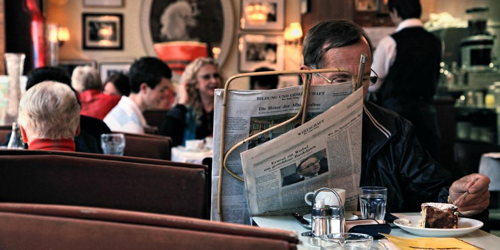 A man reading the newspaper and eating cake in a Vienna coffeehouse