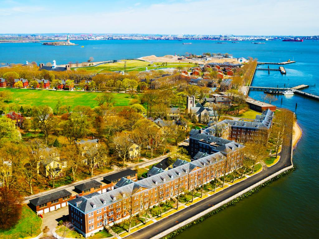 An aerial view of Governors Island in Upper New York Bay with beautiful American Architectural buildings, green fields, and trees, Manhattan area, New York City