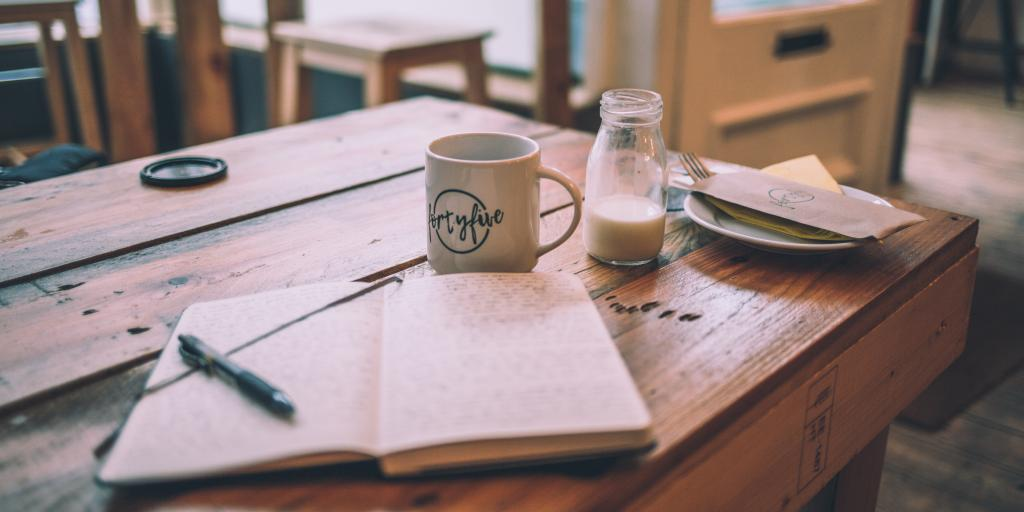 A journal open on a wooden table with a mug and a small jar of milk next to it