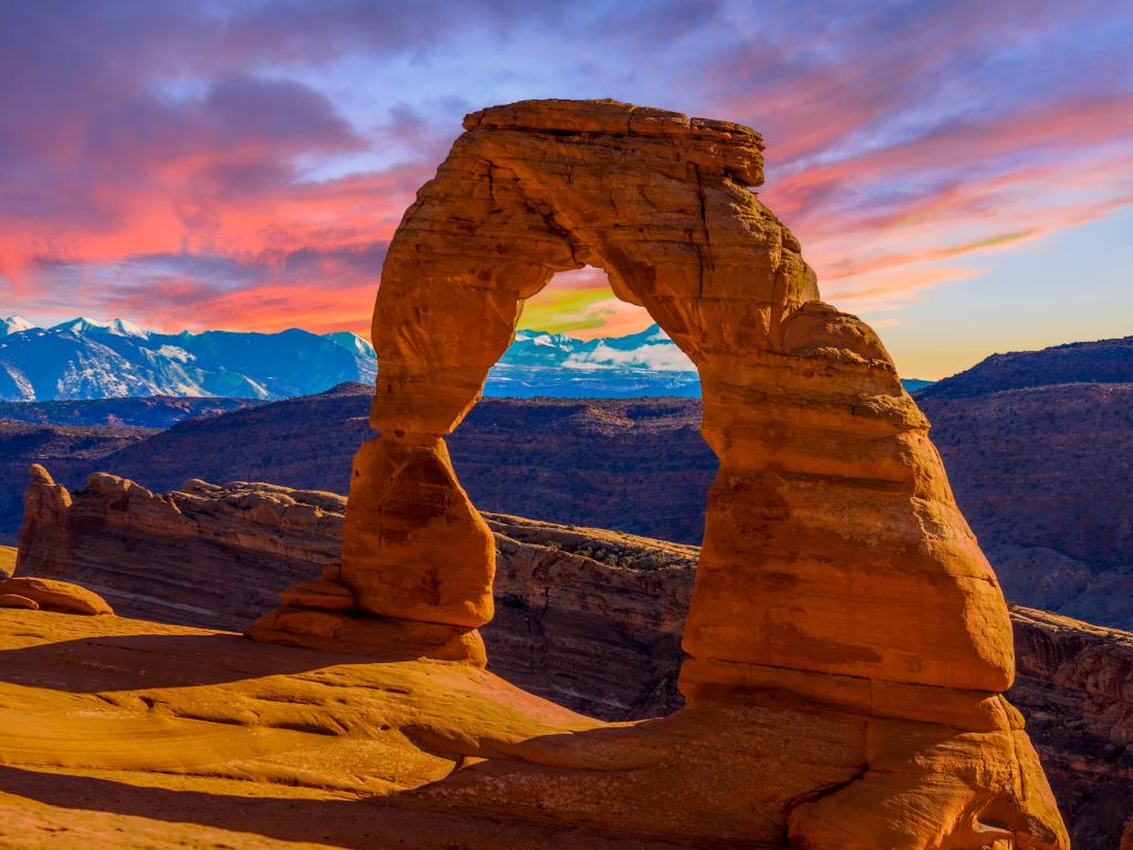 An image of a sandstone arch at Arches National Park during sunset.